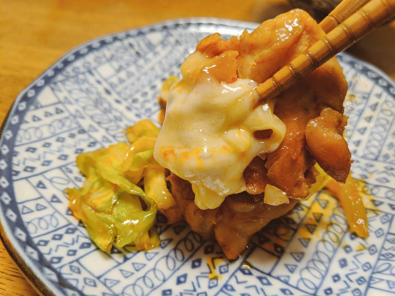 チーズタッカルビの鶏肉をチーズに絡めて箸上げしている画像