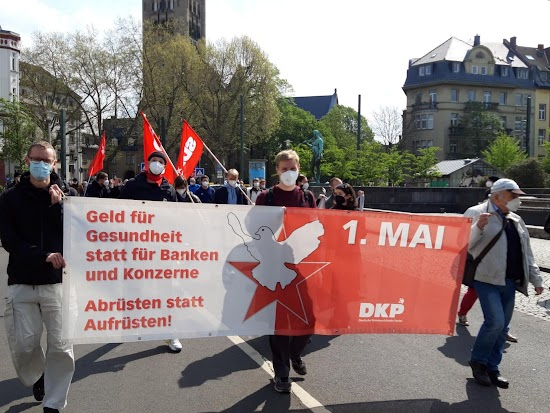 Denonstanten mit Plakat: «Geld für Gesundheit statt für Banken und Konzerne. Abrüsten statt Aufrüsten! 1. Mai DKP».