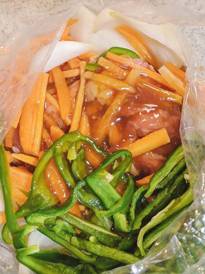 玉ねぎ、ビーマン、にんじんを細切りにし、牛肉とビニール袋に入れプルコギの素を入れた画像