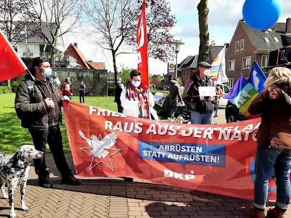 Demonstrierende mit Luftballon, Fahnen, Hund und Transparent: «... Raus aus der NATO! Abrüsten statt aufrüsten! DKP».