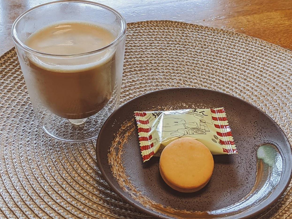 小皿に乗せた塩バタかまん1個と左にアイスコーヒーの画像