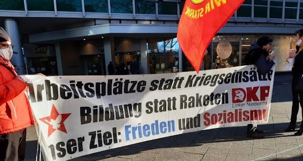 Demonstrierende mit Transparent «Arbeitsplätze statt Kriegseinsätze! Bildung statt Raketen! Unser Ziel: Frieden und Sozialismus. DKP».