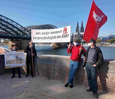 Eine Gruppe vor Kölner Kulisse hält Transparente «Grüße aus dem Braunkohlerevier Köln» und «Alle Dörfer bleiben Vergesellschaftet die RWE»