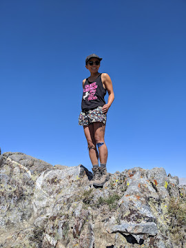 Narinda stands in shorts, a tanktop, and hiking boots on a rocky outcrop on the Nüümü Poyo. She has peeling kinesiotape on both knees.