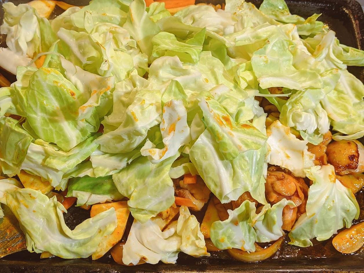 炒めた鶏肉の上にキャベツをモリモリに乗せている画像