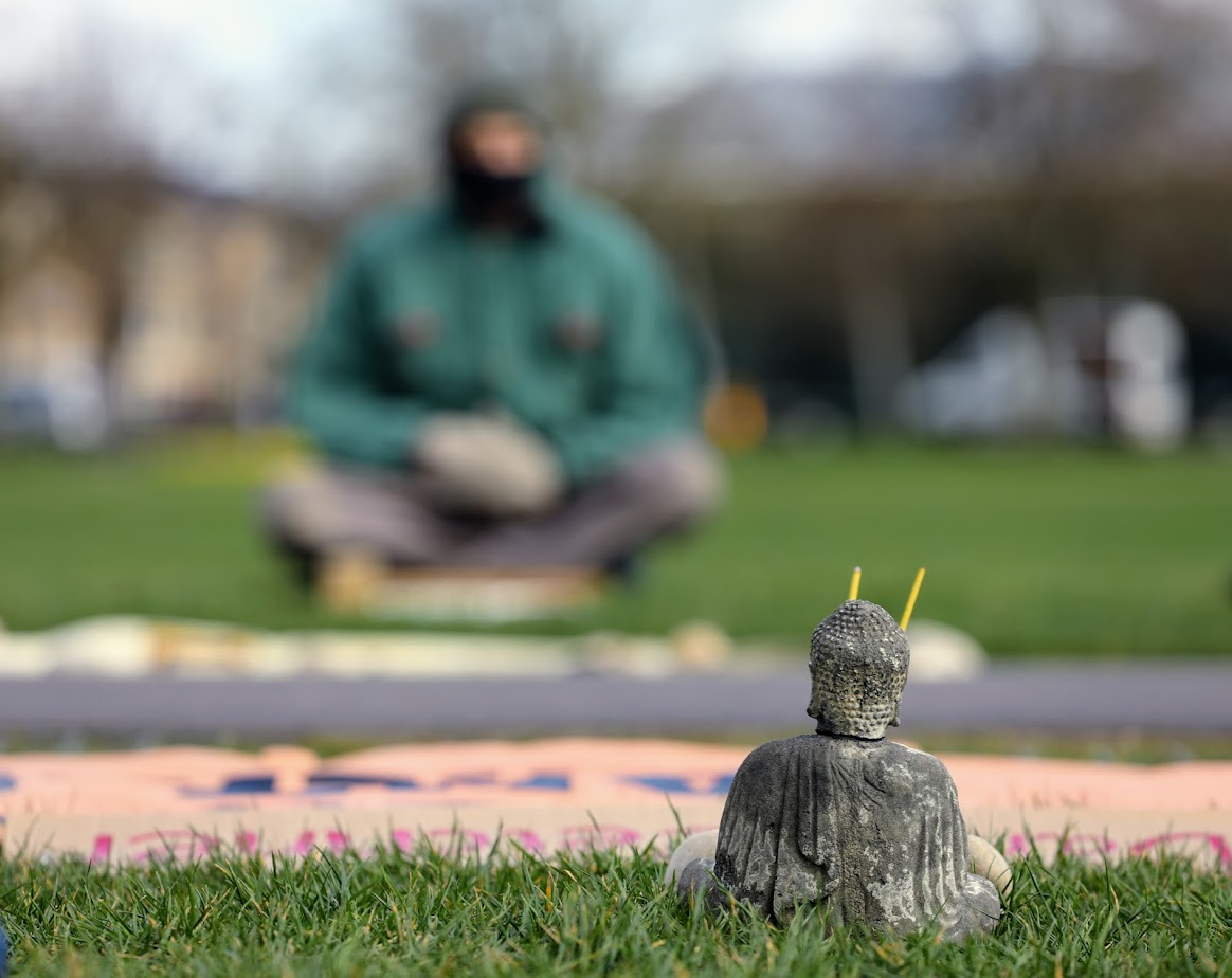 A small Buddha statue on the grass.
