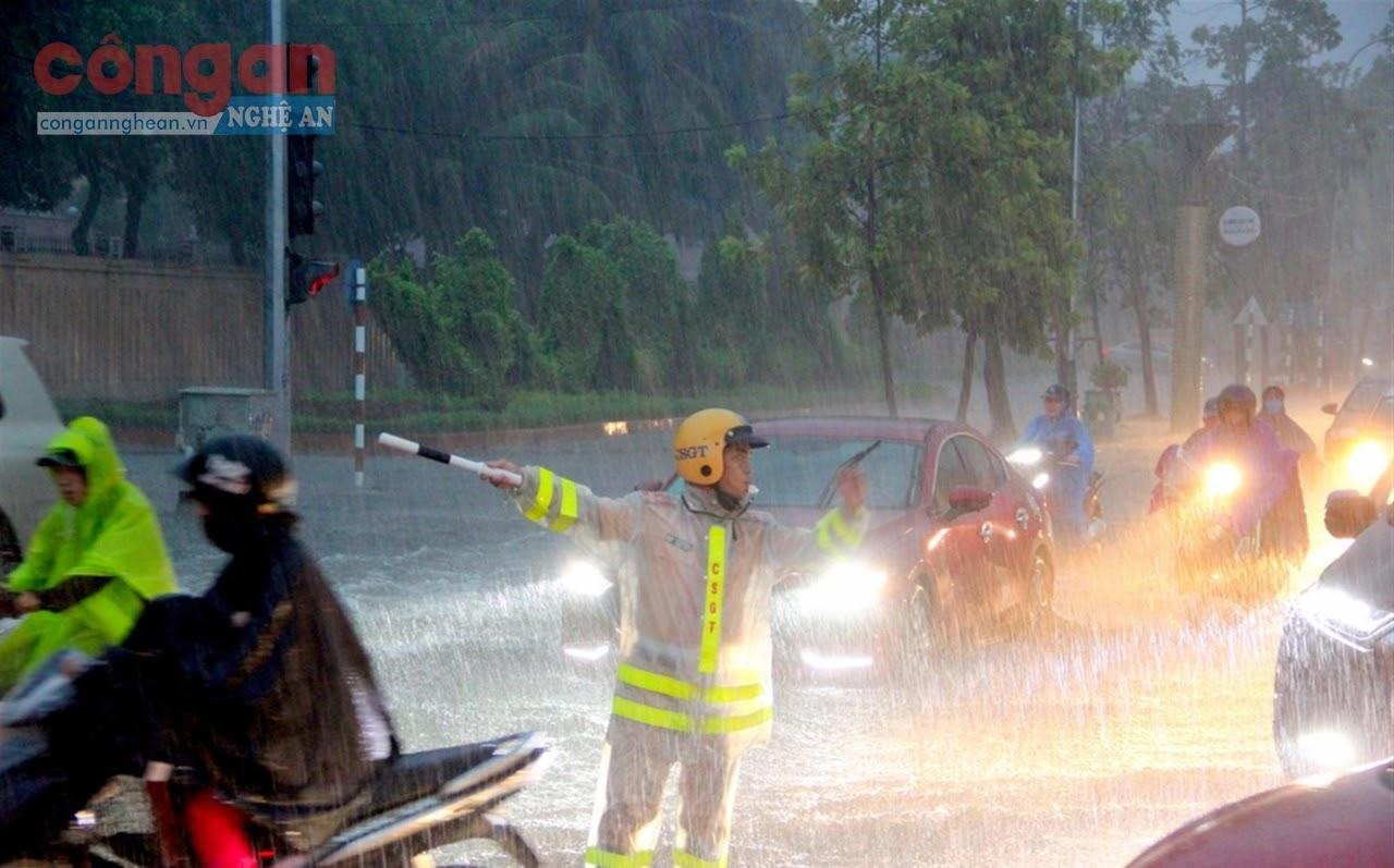 Cảnh sát giao thông Công an TP Vinh điều tiết giao thông trong mưa lớn, nước ngập - Ảnh: Quang Anh