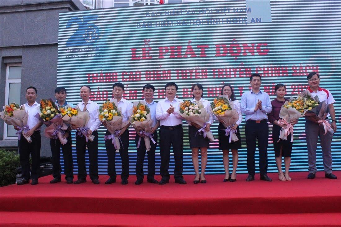 Đồng chí Bùi Đình Long, Phó Chủ tịch UBND tỉnh và đồng chí Lê Trường Giang, Giám đốc BHXH tỉnh tặng hoa cho đại diện các cơ quan, đơn vị, doanh nghiệp ủng hộ sổ BHXH, thẻ BHYT cho hộ nghèo và người dân có hoàn cảnh khó khăn