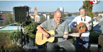 Zwei Liedermacher mit Gitarren, Lautsprecher auf dem Dach.