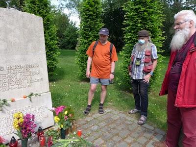 Gedenkende an Gedenkstein mit Blumenschmuck.