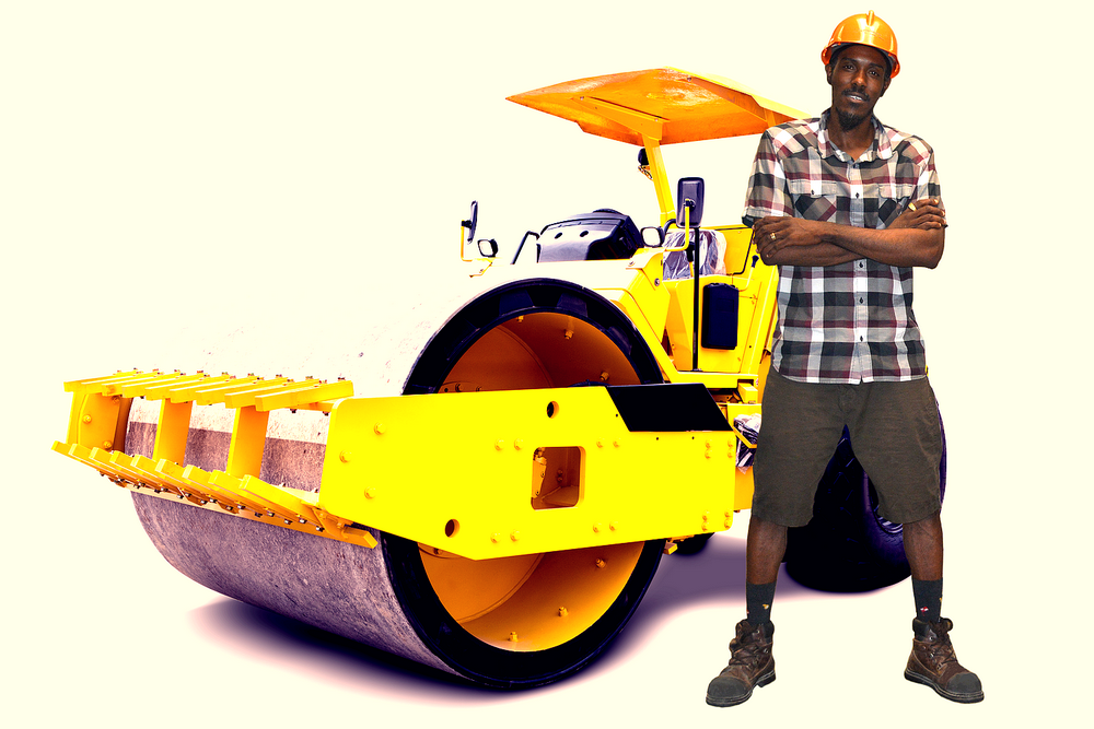 man wearing hard hat and shorts standing next to a construction steam roller