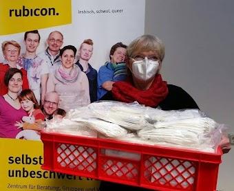 Frau trägt Korb mit Masken, hinter ihr ‹rubicon›-Plakat.