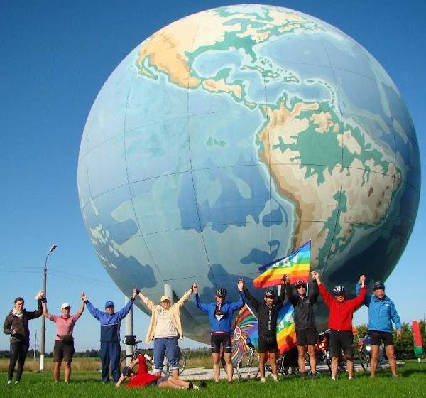Friedensradlerinnen mit Fahnen fassen sich an den Händen vor riesiger Darstellung der Erde.