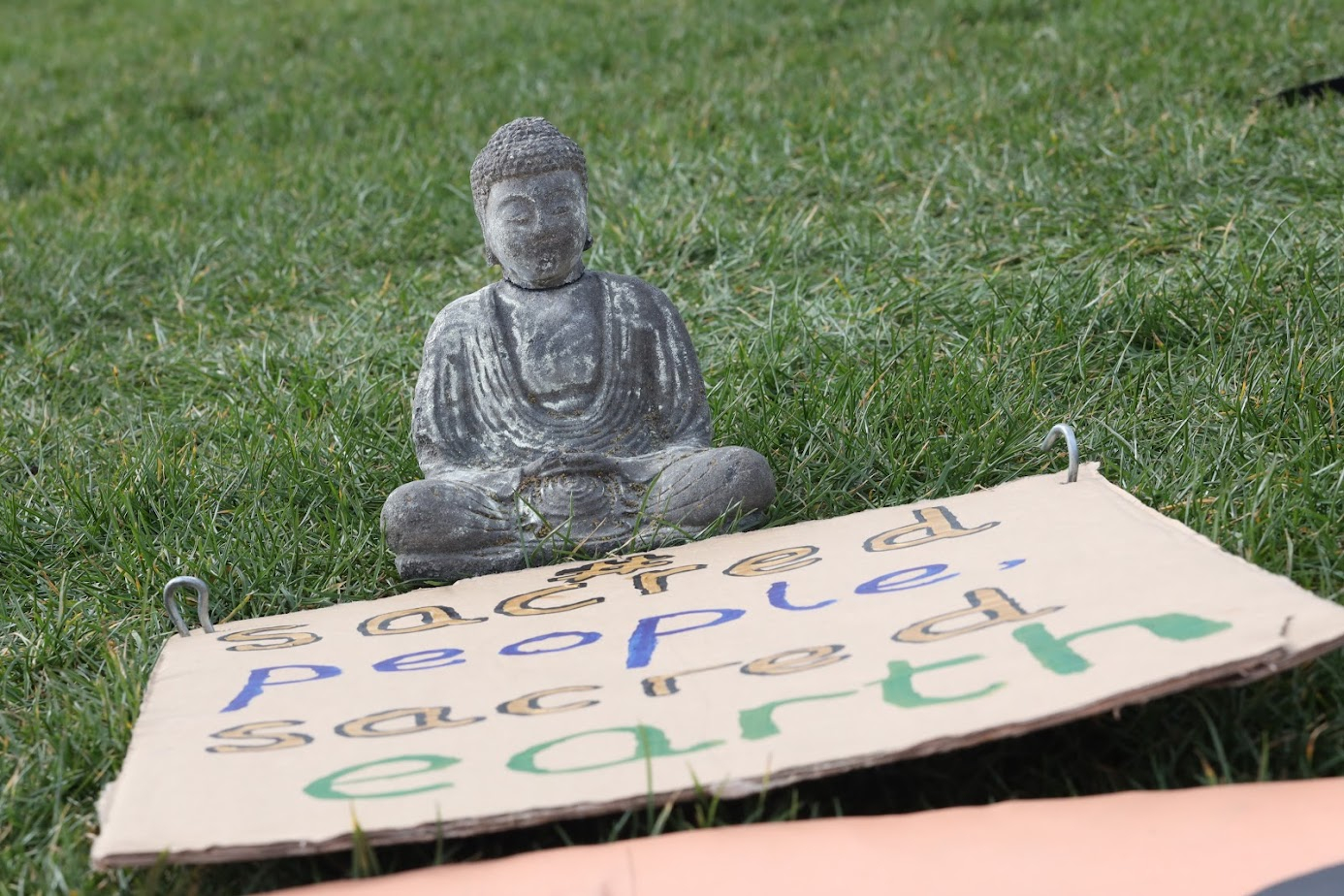 A small Buddha statue and a handmade sign which reads 'sacred people, sacred earth'.