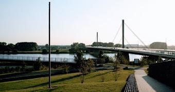 Hügelige Grünfläche, Spazierweg, Autobahnbrücke.