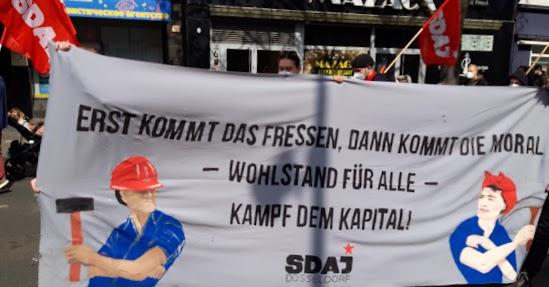 SDAJ-Fahnen und Transparent: «Erst kommt das Fressen, dann kommt die Moral – Wohlstand für Alle – Kampf dem Kapital!».