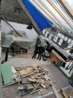Zerstörte Dachgeschoss-Wohnung. Möbel notdürftig mit Planen bedeckt.