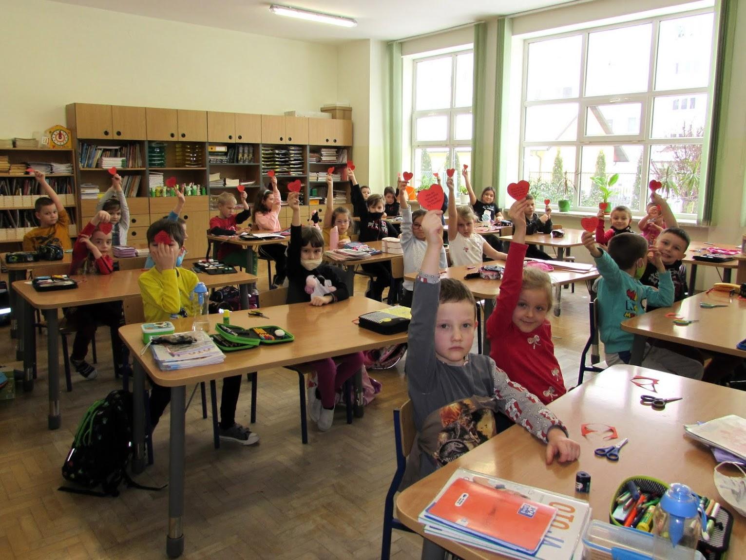 Dzieci trzymające papierowe serca w klasie.