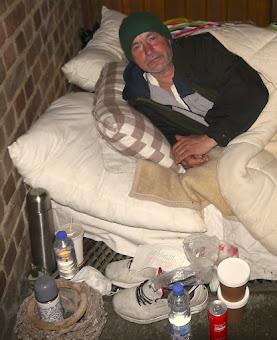 Obdachloser auf Matratze.