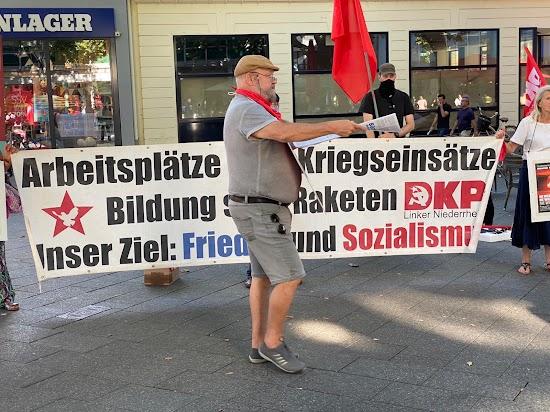 Friedensaktionist:innen, rote Fahnen, Transparent: «Arbeitsplätze statt Kriegseinsätze ... DKP».
