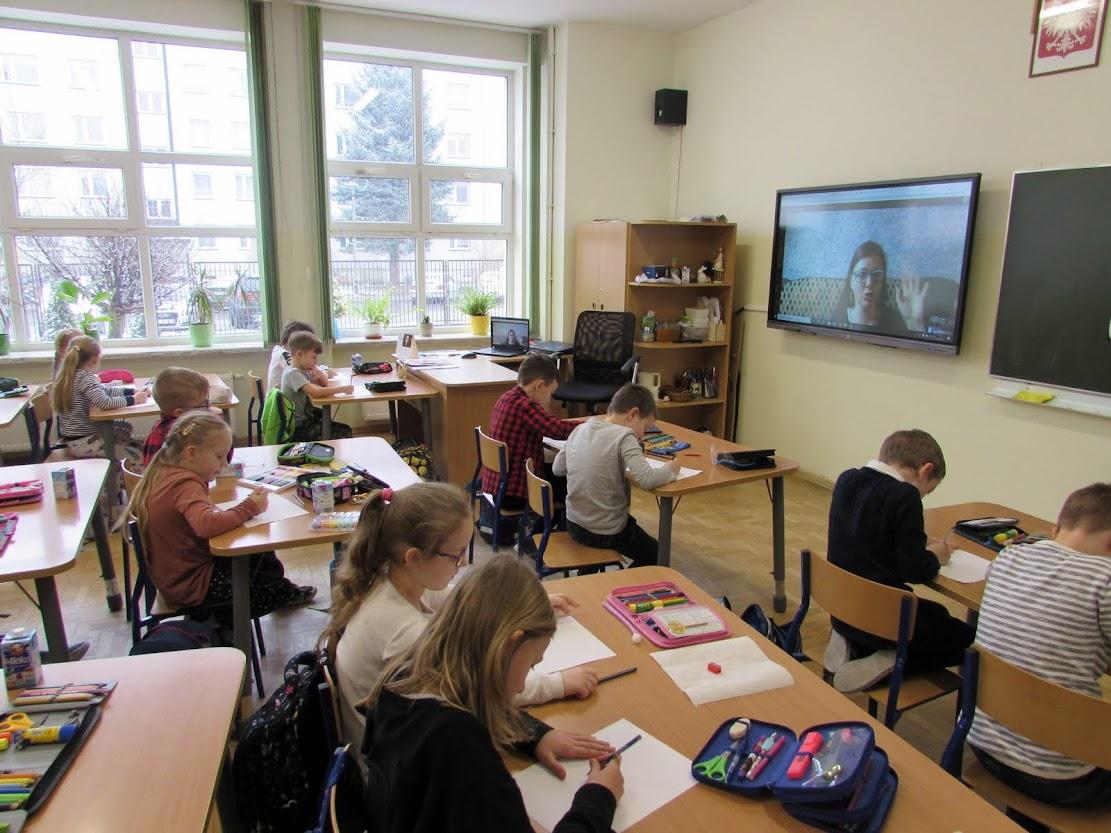 Uczniowie w klasie uczestniczący w warsztatach online.
