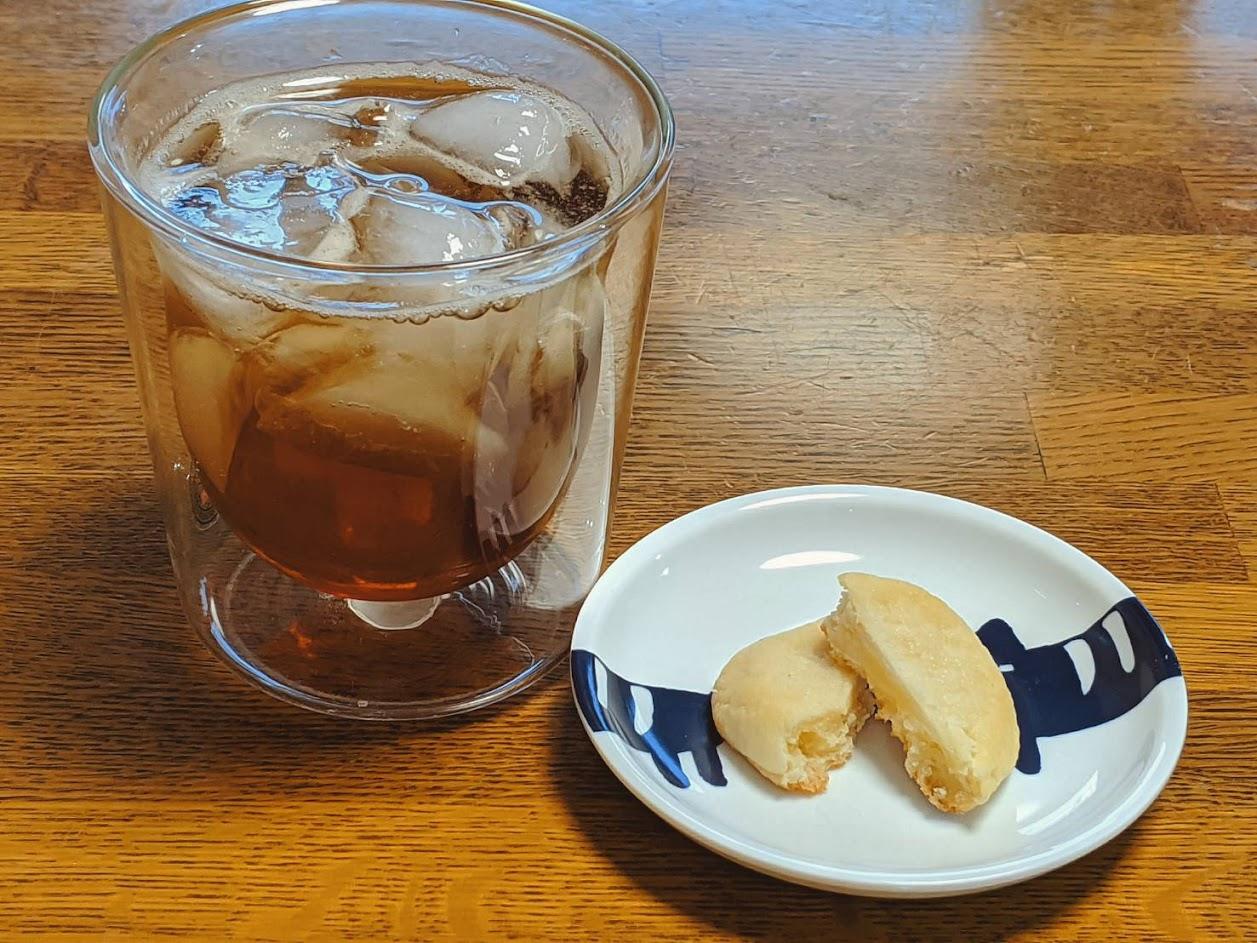 左側にアイスティー右に小皿に入った白いカントリーマアム1個の画像