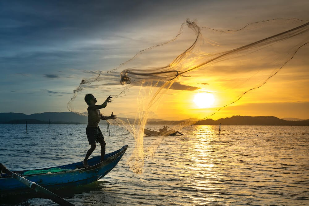 person-throwing-fish-net-while-standing-on-boat feature image for I don't want to work.jpg