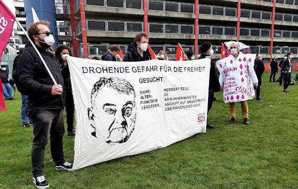 Demonstrierende mit Transparent: Karikatur, «Drohende Gefahr für die Freiheit. Gesucht: Herbert Reul, 65, NRW-Innenminister. Angriff auf Grundrechte Überwachungswahn».