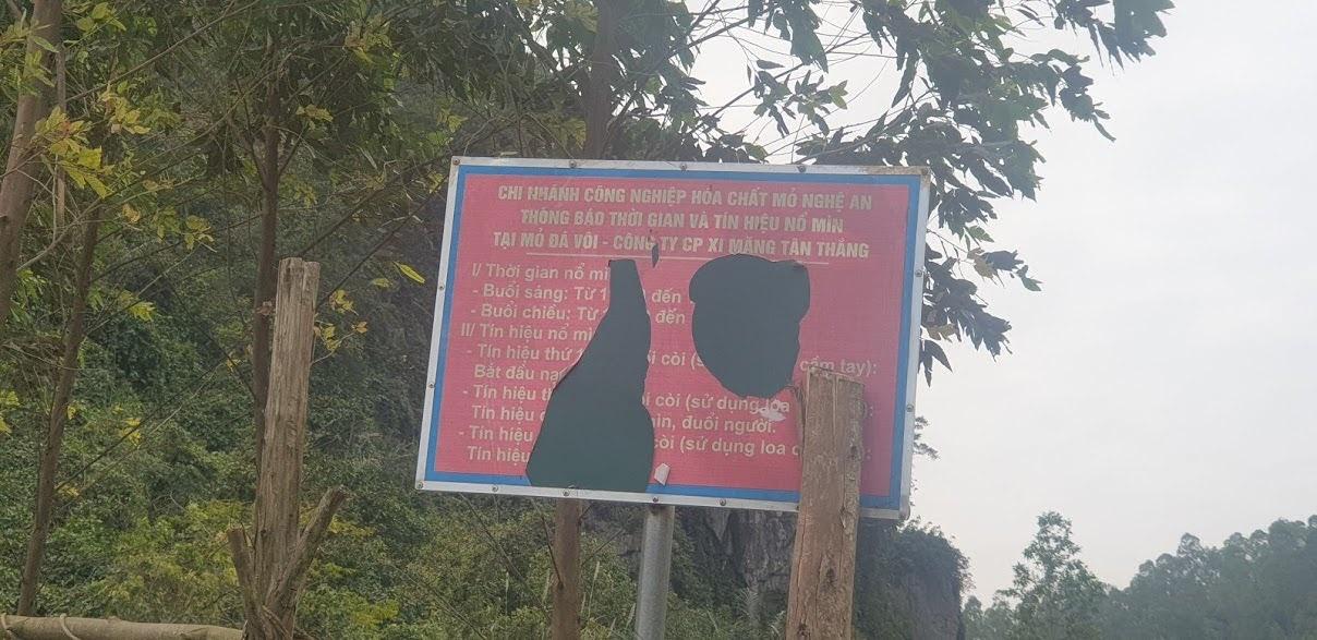 Một tấm biển cảnh báo nổ mìn sơ sài, thủng lỗ chỗ được dựng lên…