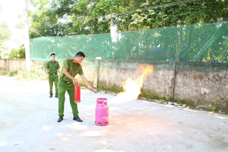 Cán bộ Đội Cảnh sát QLHC về TTXH Công an huyện Quỳ Châu hướng dẫn sử dụng, thực hành cách sử dụng bình chữa cháy để dập tắt đám cháy