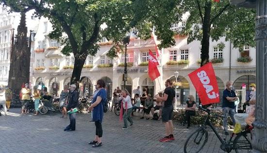 Demonstrant;innen mit SDAJ- und DKP-Fahne.