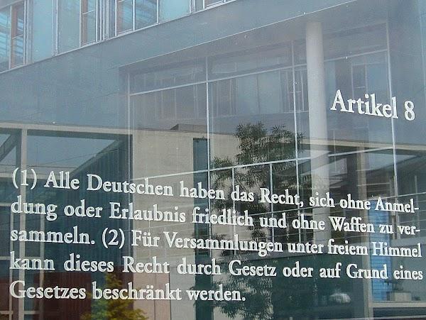 Schrift auf Glasscheibe: «Artikel 5. (1) Alle Deutschen haben das Recht, sich ohne Anmeldung oder Erlaubnis friedlich und ohne Wadfen zu versammeln. (2) Für Versammlungen unter freiem Himmel kann dieses Recht durch Gesetz oder auf Grund eines Gesetzes beschränkt werden.».