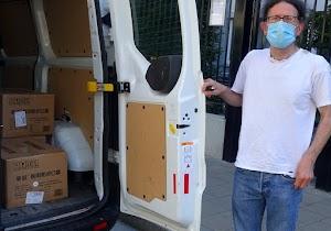 Botschaftsmitarbeiter mit Maske am bepackten Lieferwagen.