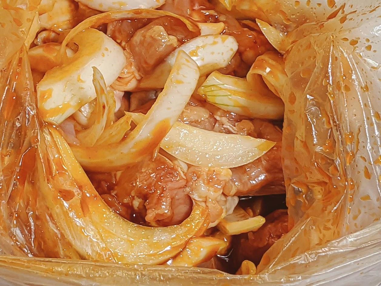 ビニール袋に鶏肉とたまねぎとタレを入れもみ込んだ画像