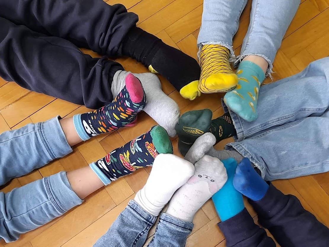 Zdjęcie przedstawia nogi dzieci, na stopach mają założone skarpetki nie od pary.