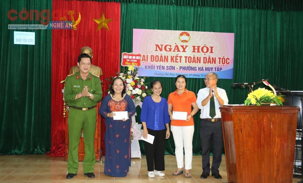 Thượng tá Nguyễn Đức Cường, Trưởng Công an TP Vinh        tặng quà cho người dân trong Ngày hội đại đoàn kết                       toàn dân tộc tại phường Hà Huy Tập