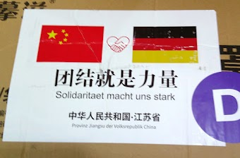 Kartons aus China, Aufkleber mit chinesischer und deutscher Flagge, dazwischen Solidaritätssymbol (Händeschütteln in Herzform) «Solidarität macht uns stark. Provinz Jiangsu der Volksrepublik China.».
