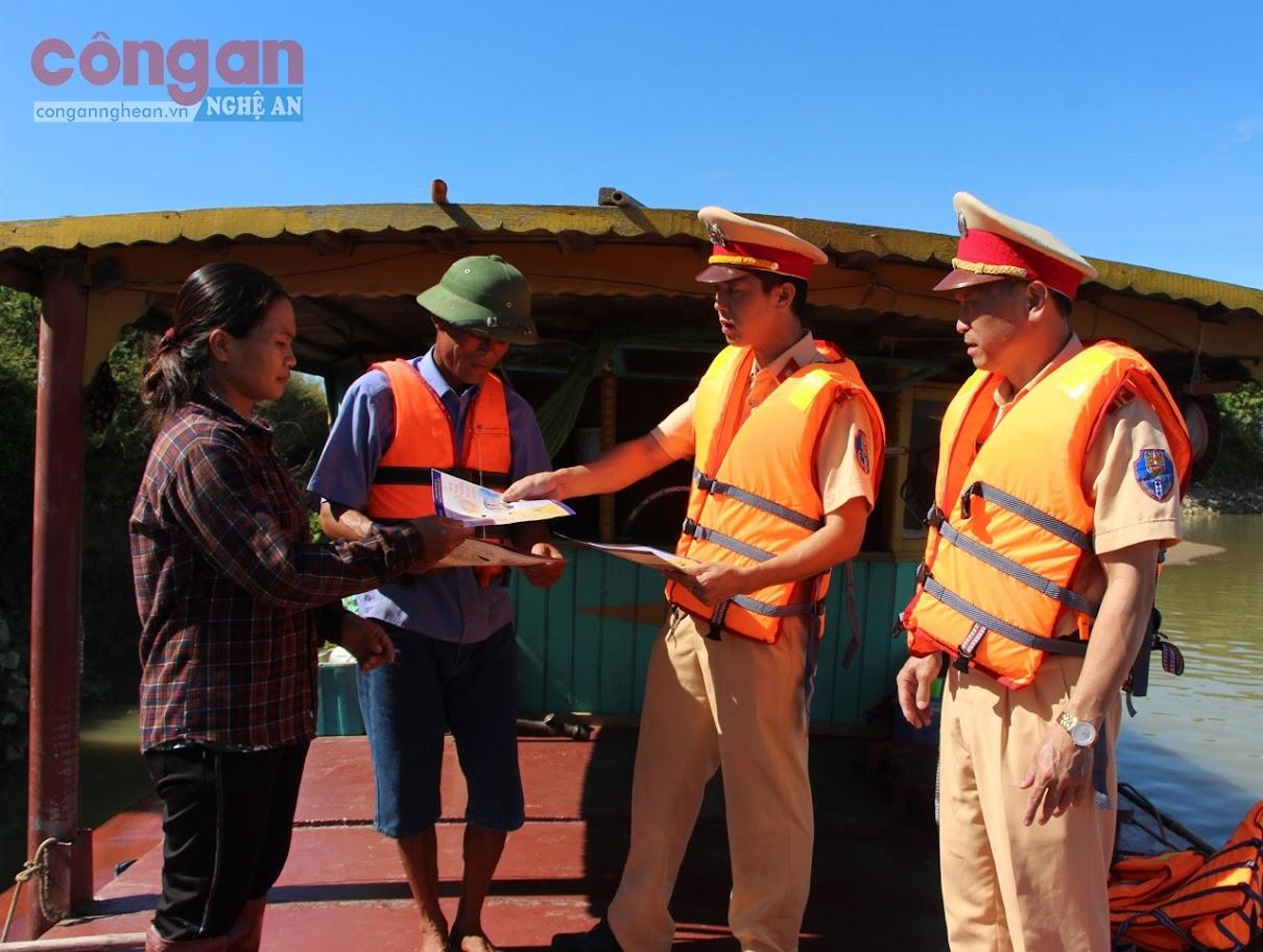 Đội Cảnh sát Đường Thủy thuộc Phòng CSGT Công an tỉnh phát tờ rơi tuyên truyền về Luật Giao thông đường thủy nội địa cho chủ các phương tiện thủy hoạt động trên tuyến sông Lam