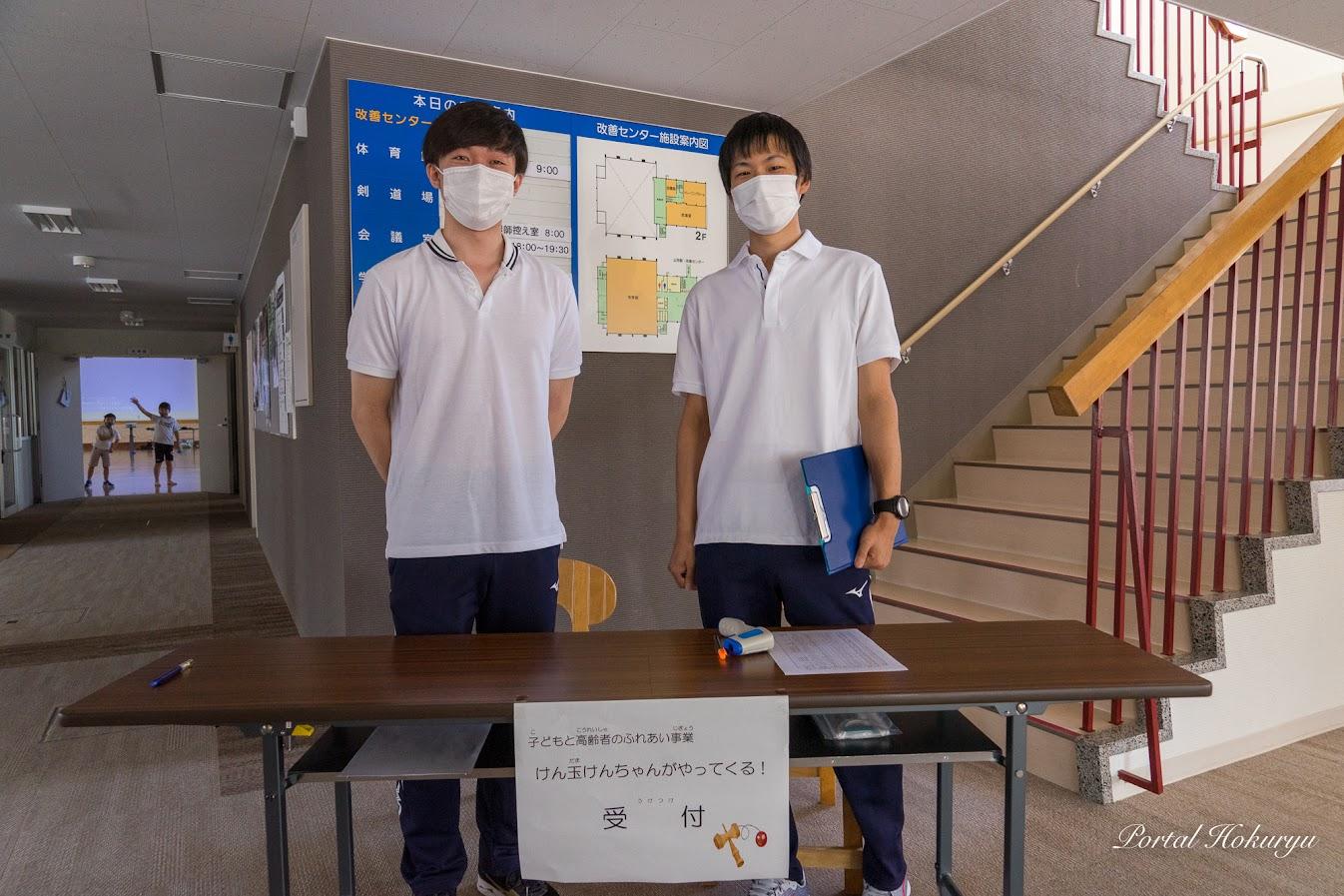 受付で検温実施:北竜町教育委員会職員・岸直樹さん(右)、清水野梨希さん(左)