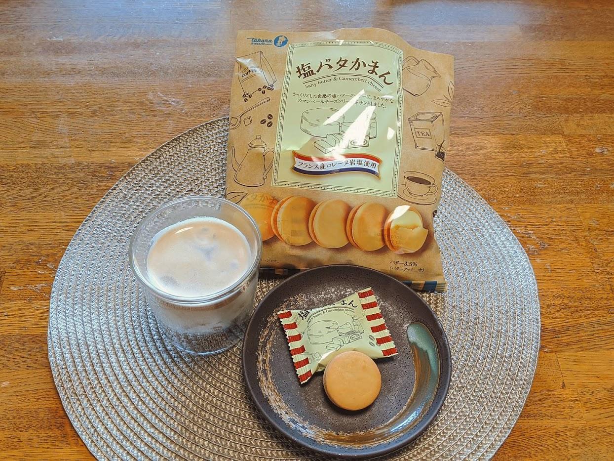 プレイスマットの上に左から時計回りにアイスコーヒー、塩バタかまんの袋、小皿に乗せた塩バタかまんの画像