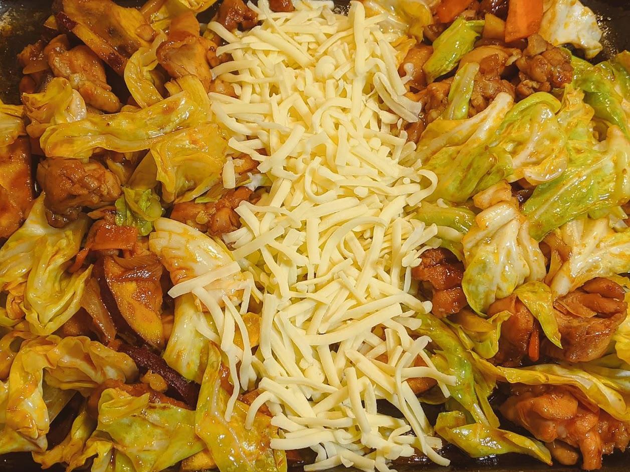 鉄板の上の野菜を両脇に避けて真ん中にチーズを乗せている画像