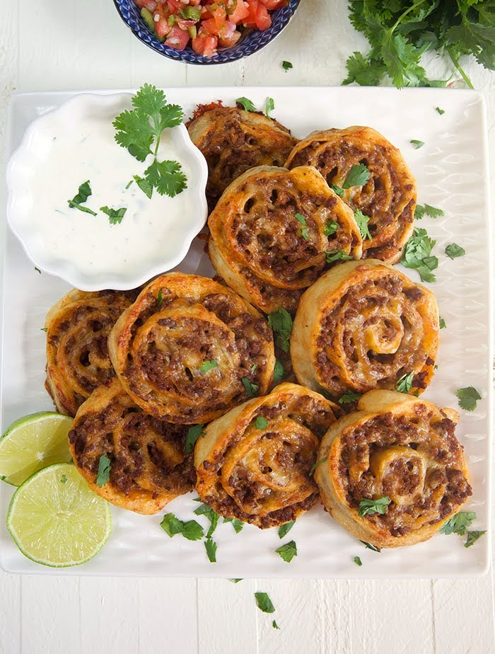 Taco pinwheels on a square white platter with a white bowl of dipping sauce and a sliced lime.