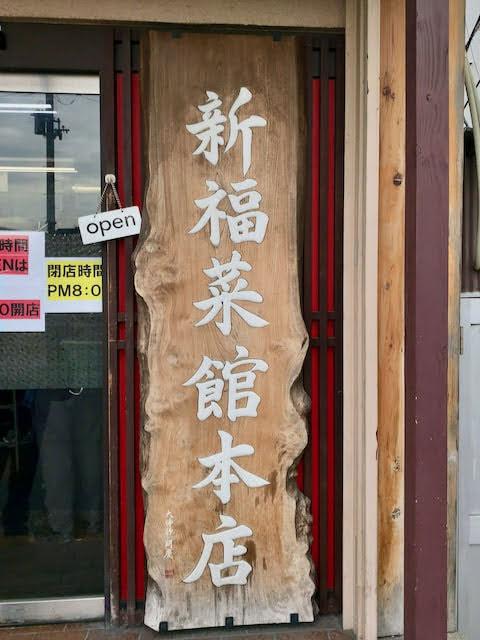 店頭の看板「新福菜館本店」と書かれてる