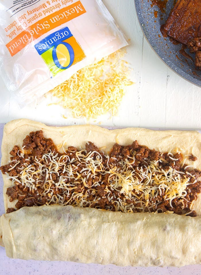 pizza dough with taco beef and cheese being rolled up.