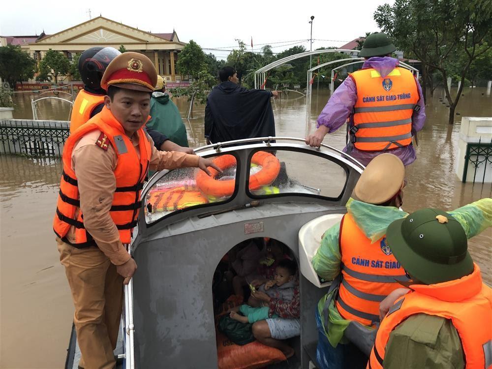 Cán bộ, chiến sỹ Công an Nghệ An phối hợp cùng Công an Hà Tĩnh giúp đỡ người dân bị ngập lụt đến nơi an toàn