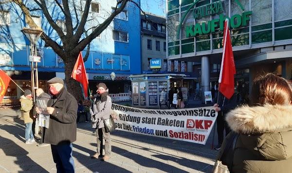 Demonstrierende mit Fahnen und Transparent «Arbeitsplätze statt Kriegseinsätze! Bildung statt Raketen! Unser Ziel: Frieden und Sozialismus. DKP».