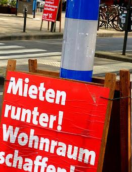 Plakattafel am Straßenrand. «Mieten runter! Wohnraum schaffen!».