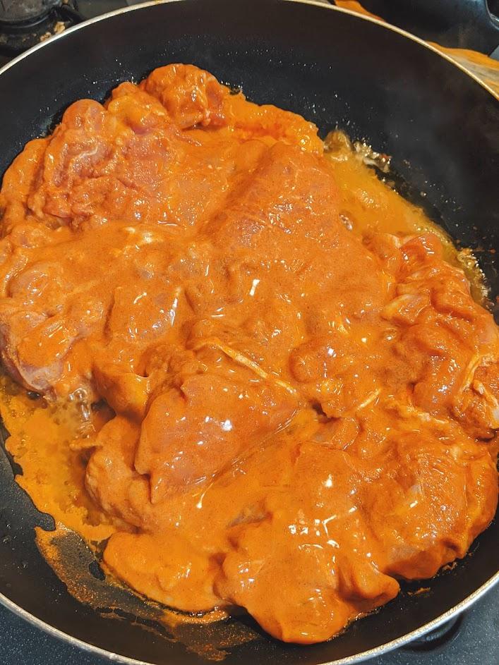 フライパンに漬け込んだ鶏肉を2枚入れている画像