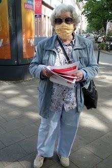 Flugblattverteilerin mit Sonnenbrille und Mund-Nasenschutzmaske. Vermummungsverbot? Das war mal. – Vermummungsgebot.