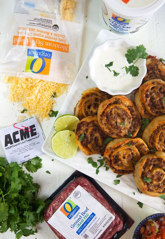 taco pinwheels on a square platter with a package of shredded cheese, a receipt from ACME and a package of ground beef.